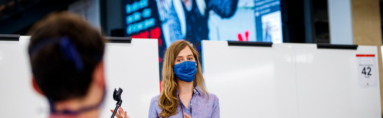 Woman teaching a class with a mask on and and a large display behind her.